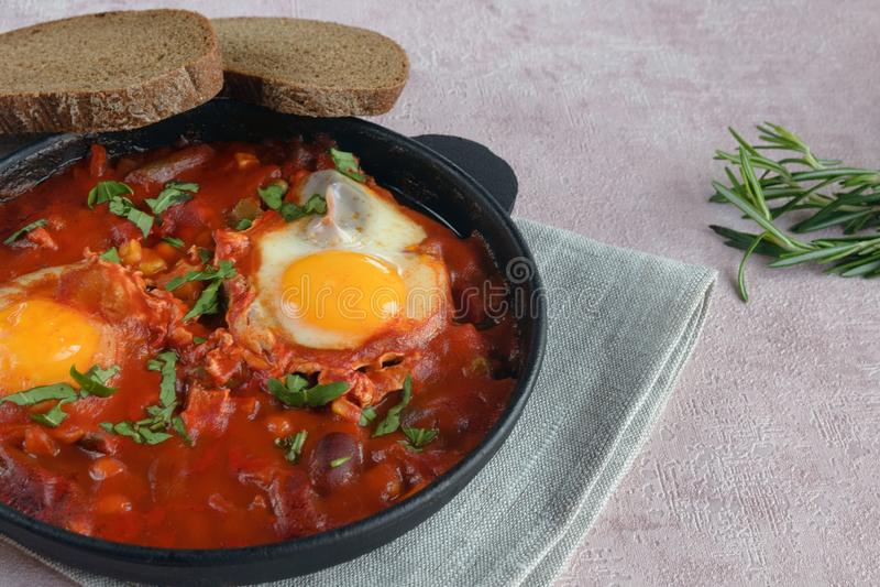Shakshuka es un plato oriental tradicional de huevos, de tomates frescos, del ajo, de especias, del aceite de oliva y de hierbas fotos de archivo