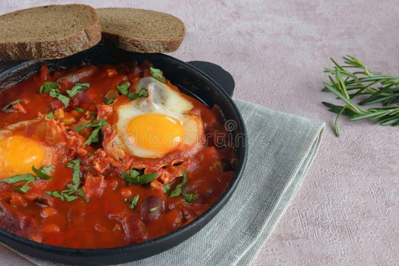 Shakshuka ist ein traditioneller orientalischer Teller von Eiern, von frischen Tomaten, von Knoblauch, von Gewürzen, von Olivenöl stockfotos