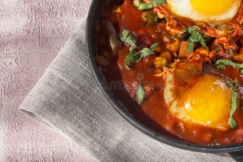 Shakshuka jest smakowitym naczyniem jajka, smażącym w kumberlandzie pomidory, gorący pieprz, cebula i podprawy na czarnej żeliwne obraz stock