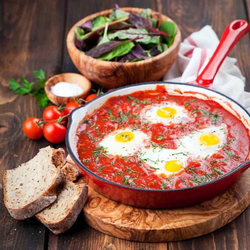 Shakshuka med tomater och ägg i en gjutjärnpanna arkivfoto