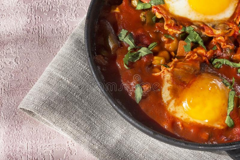 Shakshuka is a tasty dish of eggs, fried in a sauce of tomatoes, hot pepper, onion and seasonings on a black cast-iron pan. Tomato stock image