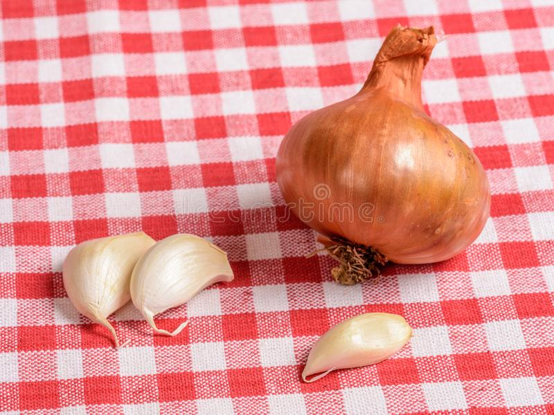 Shallot and garlic cloves on a kitchen table royalty free stock image