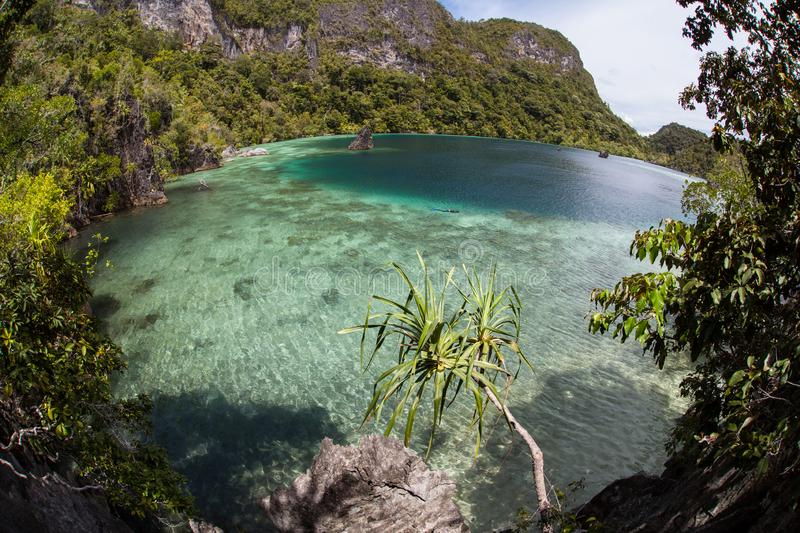 Shallow Coral Reef and Limestone Islands in Raja Ampat. A shallow and healthy reef flat fringes the rugged limestone islands of Raja Ampat, Indonesia. This stock photography