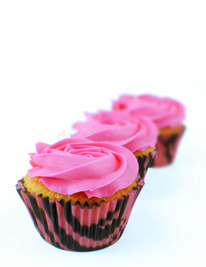 Shallow depth of field with front focus of three cupcakes decorated wtih pink, rose shaped icing on a white background. royalty free stock photo
