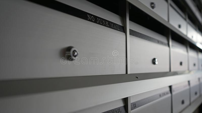 Shallow depth of focus. Angled metal grey mailboxes. stock photography