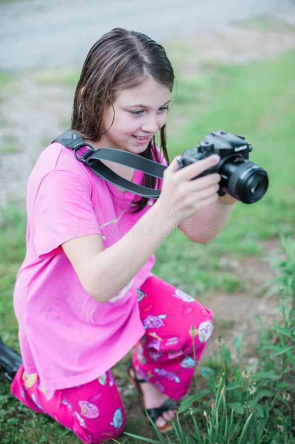 Shallow Focus Photo of a Girl in Pink Round-neck Shirt Holding Black Dslr Camera royalty free stock image
