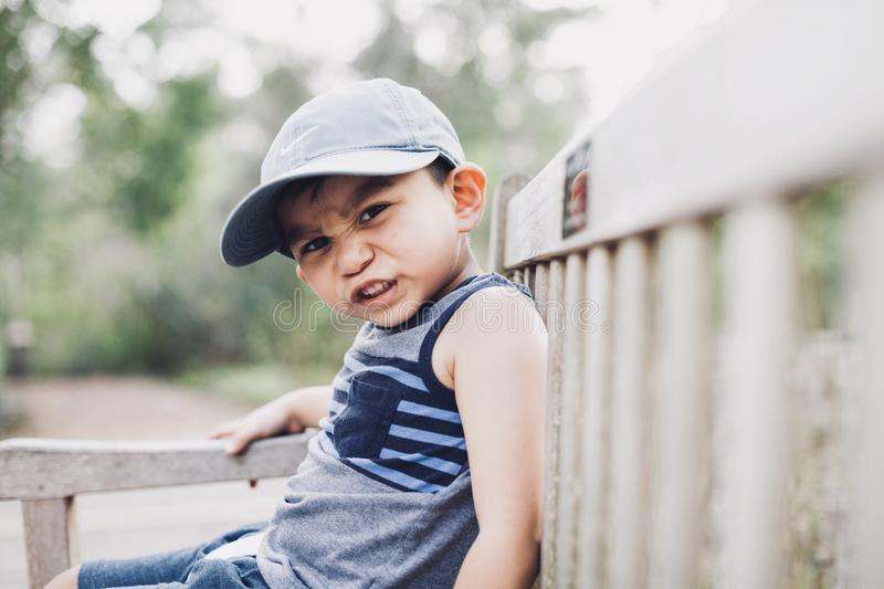 Shallow Focus Photography Of A Boy Sitting On Bench royalty free stock images