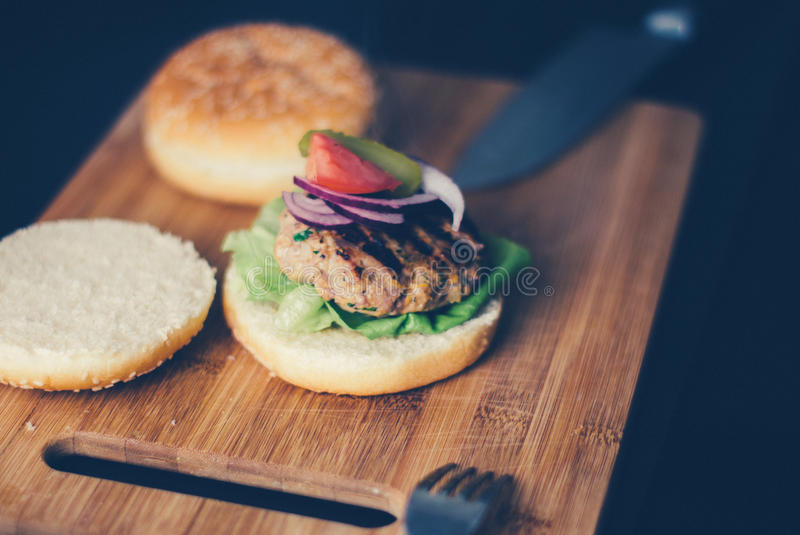 Shallow Focus Photography of Burger Sandwich Served on Brown Wooden Chopping Board royalty free stock photography