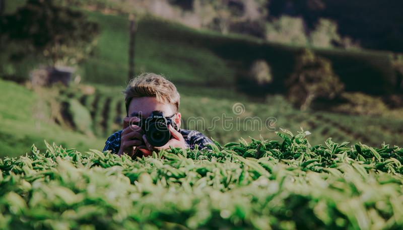 Shallow Focus Photography of Man Holding Dslr Camera stock photo