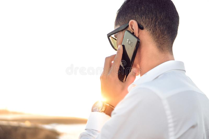 Shallow Focus Photography of a Man in White Collared Dress Shirt Talking to the Phone Using Black Android Smartphone stock photography