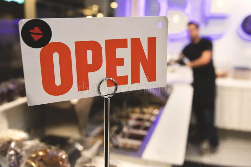 Shallow Focus Photography of Red and White Open Signage Near Man Wearing Black Shirt royalty free stock photos