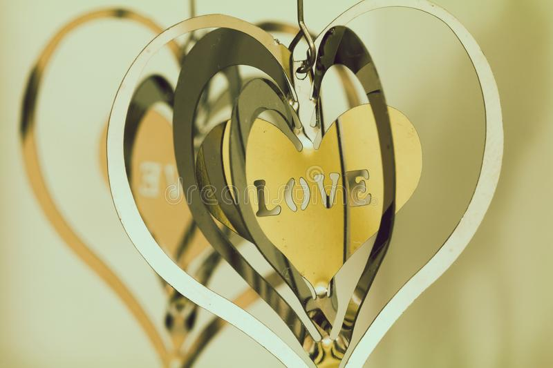 Shallow Focus Photography of Silver and Gold Heart Pendants stock photos