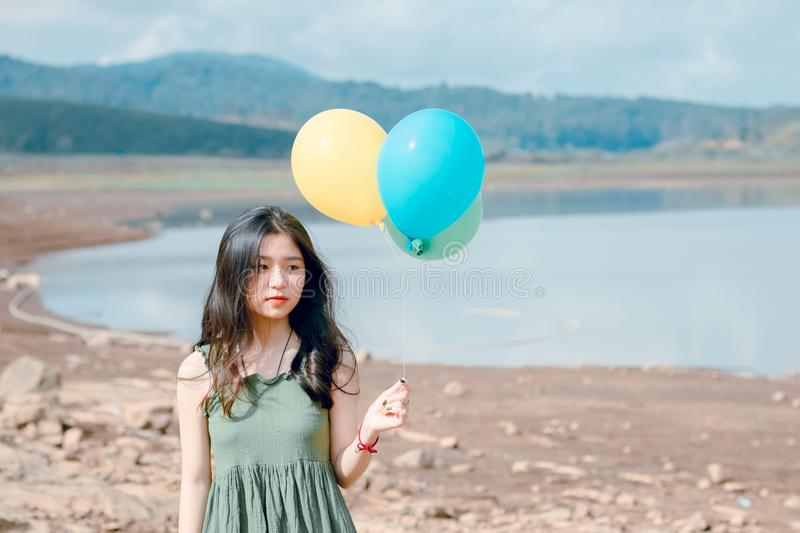 Shallow Focus Photography of Woman Holding Three Assorted-color Balloons royalty free stock photos
