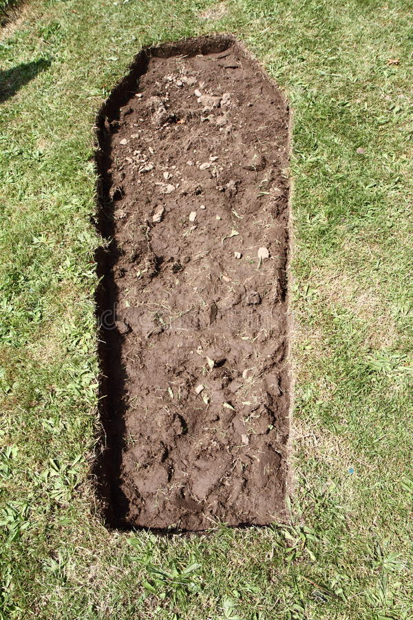 Shallow grave. Dug up, surrounded by grass stock photos