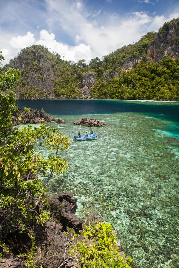 Shallow Reef Surrounded by Limestone Islands in Raja Ampat. A shallow and healthy reef flat fringes the rugged limestone islands of Raja Ampat, Indonesia. This royalty free stock photography