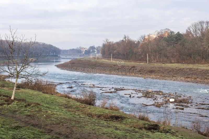 Shallow river in autumn and winter. River landscape in spring or autumn. The bend of a shallow river. Trees on the bank along the river. Picturesque autumn stock photo
