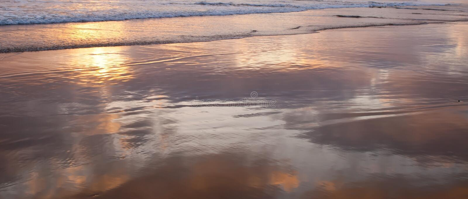 The shallow surf of the Pacific ocean in southern California, USA with the clouds reflecting off the water royalty free stock image