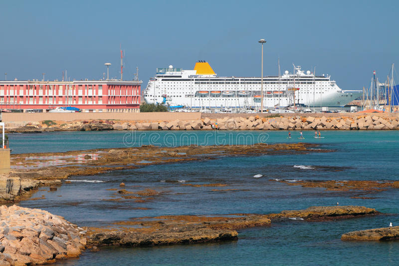 Shallow-water bay and cruise liner in port. Porto-Torres, Italy stock photos