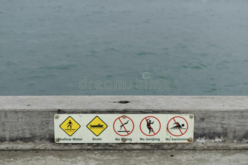 Warning signs at the edge of the pier. stock photos