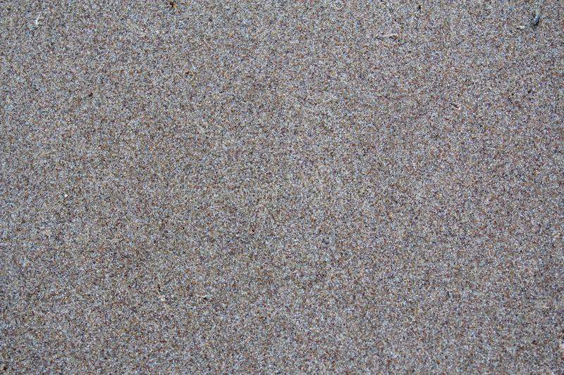 Fine gray sand. A shallow wet sandy beach on a summer evening on the river bank royalty free stock photo