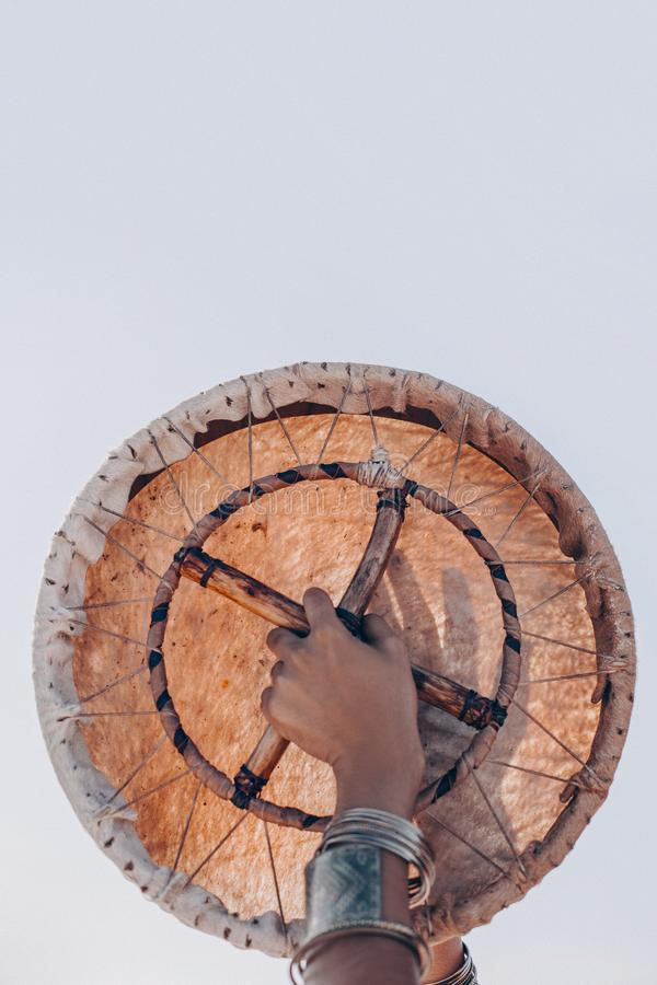 Shaman drum in woman hand. playing ethnic music royalty free stock images