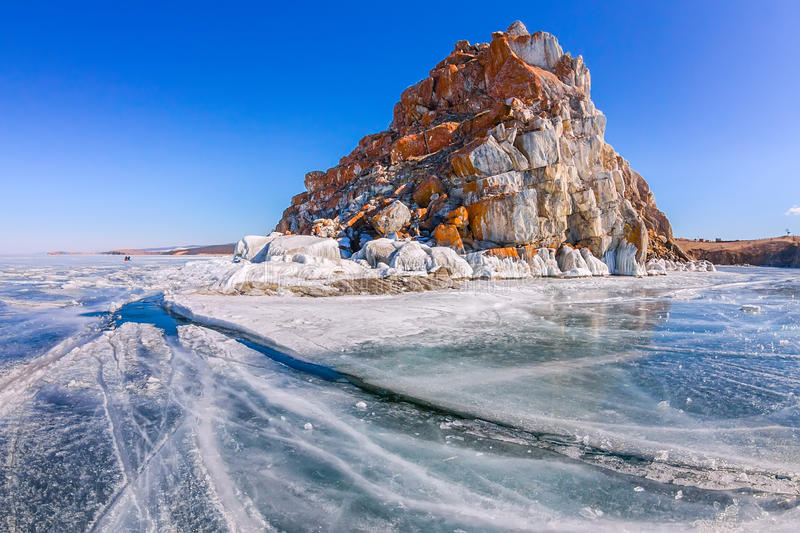 Shaman Rock or Cape Burhan on Olkhon Island in winter, surrounded by the blue ice of Lake Baikal with cracks royalty free stock images