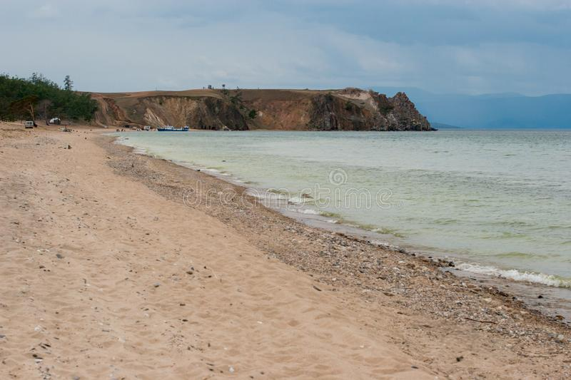 Shaman Rock on Lake Baikal in gloomy weather. Sandy shore. There is a boat near the shore. stock photos