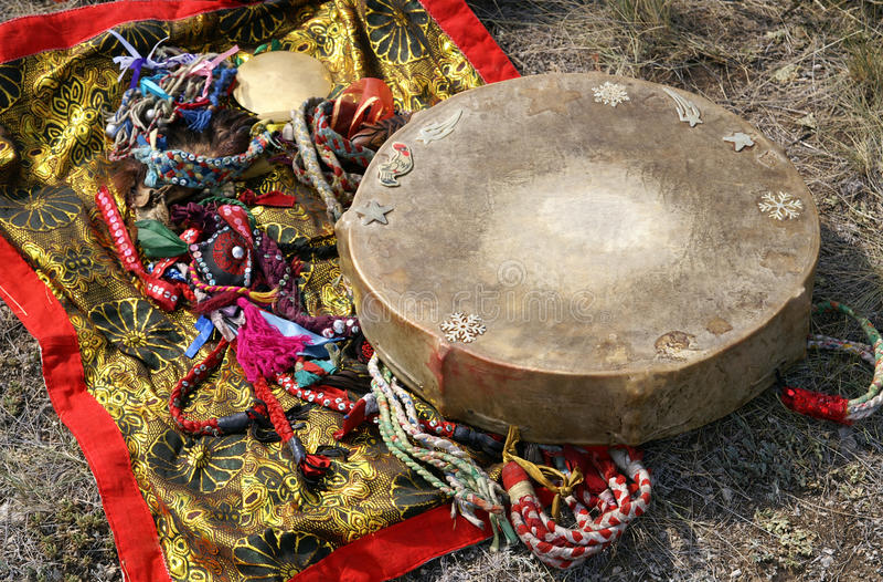 Shaman tambourine and mirror. Old shaman traditional accessories and belongings - ceremonial tambourine, shawl and mirror. Tuva, Altay, Siberia, Mongolia royalty free stock photo