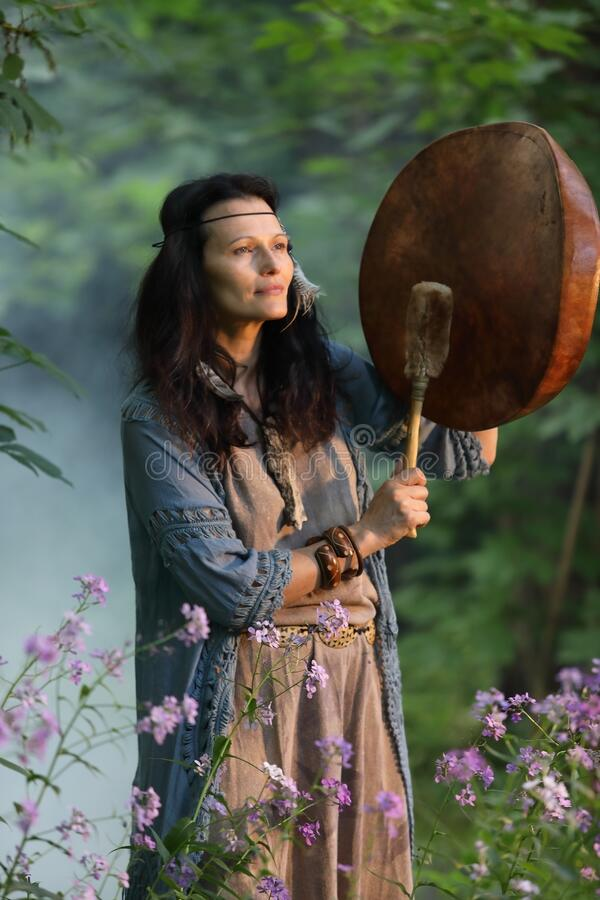 Shaman woman drumming in the evening forest stock photo