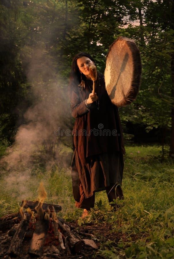 Shaman woman playing on shaman drum near large fire stock photos