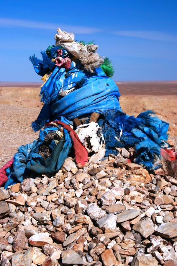 Ovoo, oboo or obo ceremonial rock pile with sacred hadags or khadags blue silk scarves with a goat skull close-up Mongolia. Shamanic ovoo, oboo or obo ceremonial royalty free stock photos
