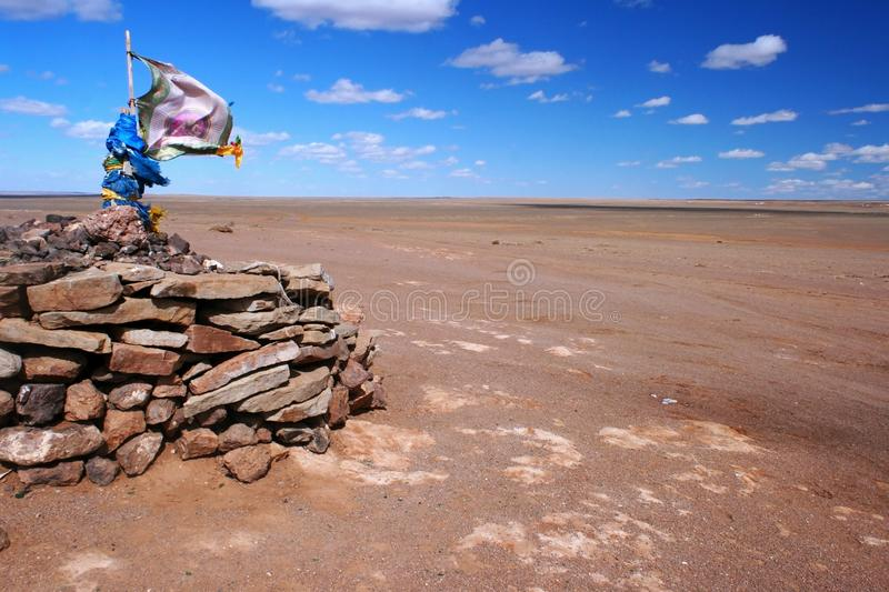 Ovoo, oboo or obo ceremonial rock pile with sacred hadags or khadags blue silk scarves and prayer flag, Gobi Desert Mongolia. Shamanic ovoo, oboo or obo stock photos