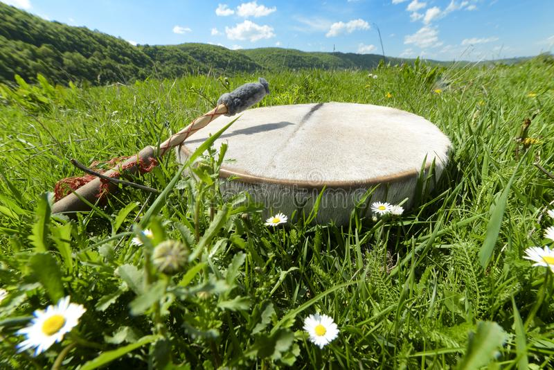 Man with a tambourine on the grass, Ukraine, May 2017. Shamanic tambourine on a meadow royalty free stock photos