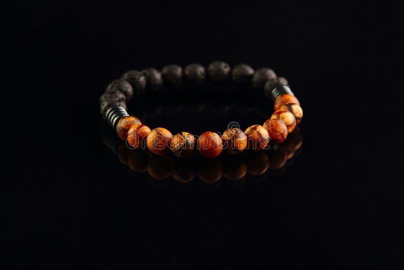 Shamballa-Armband, das vom Holz auf einem Schwarzen hergestellt wurde, spiegelte Hintergrund wider lizenzfreie stockfotografie
