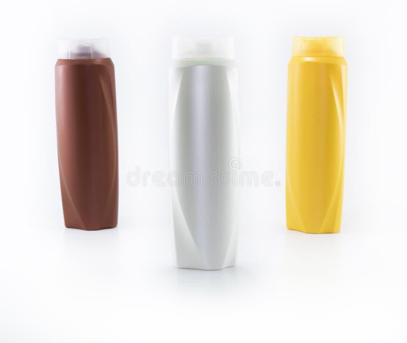 Shampoo, befeuchtende Flaschen in den braunen, wei?en, gelben Farben stockfotografie