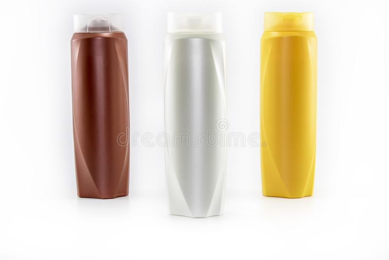 Shampoo, befeuchtende Flaschen in den braunen, wei?en, gelben Farben stockbilder