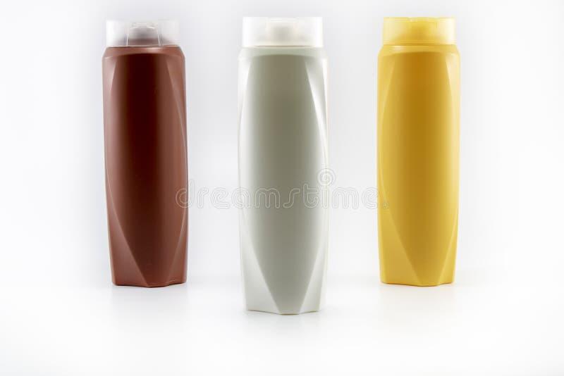 Shampoo, befeuchtende Flaschen in den braunen, wei?en, gelben Farben lizenzfreie stockbilder
