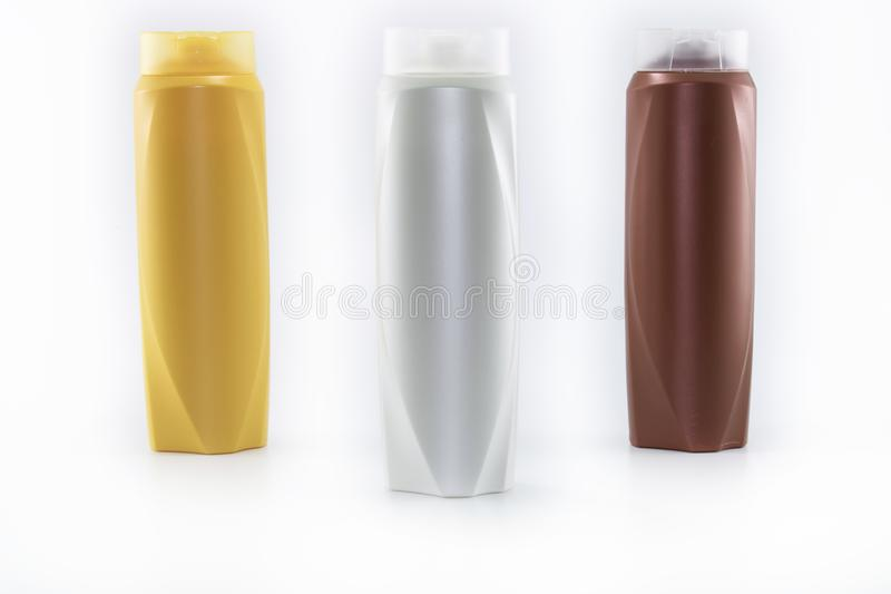 Shampoo, bevochtigende flessen in bruine, witte, gele kleuren royalty-vrije stock fotografie