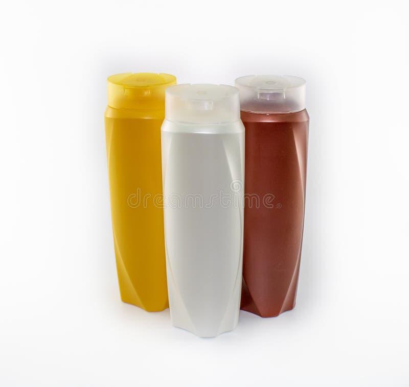 Shampoo, bevochtigende flessen in bruine, witte, gele kleuren stock afbeeldingen