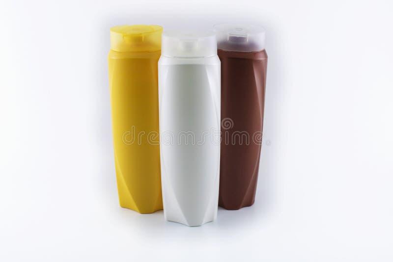 Shampoo, bevochtigende flessen in bruine, witte, gele kleuren stock foto's
