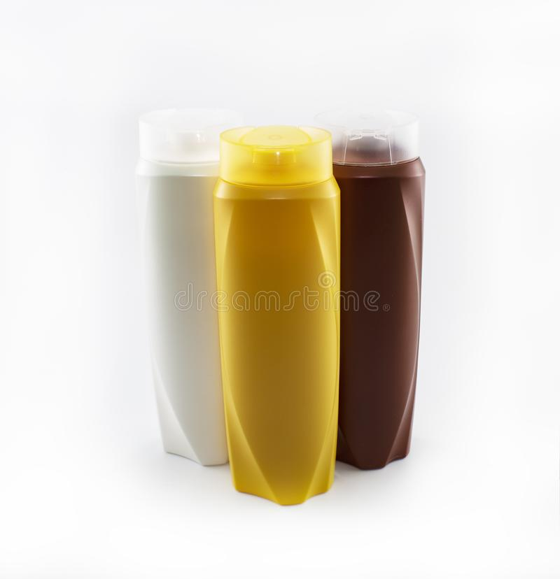 Shampoo, bevochtigende flessen in bruine, witte, gele kleuren royalty-vrije stock afbeelding