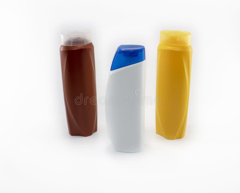 Shampoo, bevochtigende flessen in bruine, witte, gele kleuren royalty-vrije stock afbeeldingen