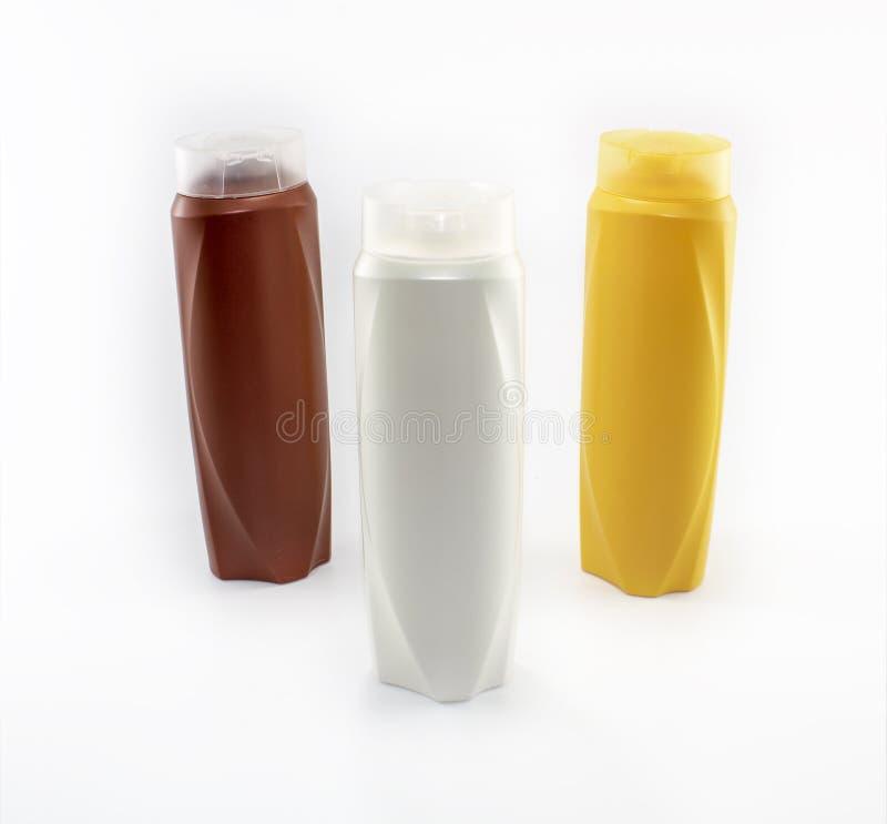Shampoo, bevochtigende flessen in bruine, witte, gele kleuren stock fotografie