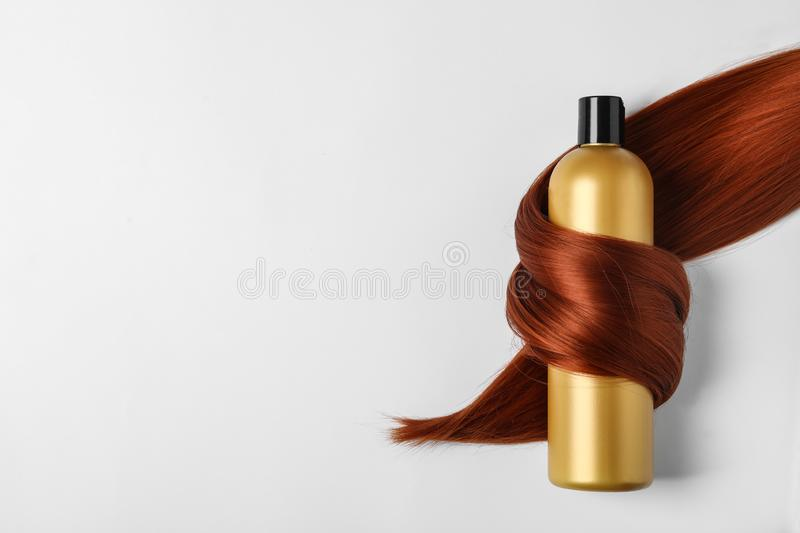 Shampoo bottle wrapped in lock of hair  on white. Natural cosmetic products royalty free stock images