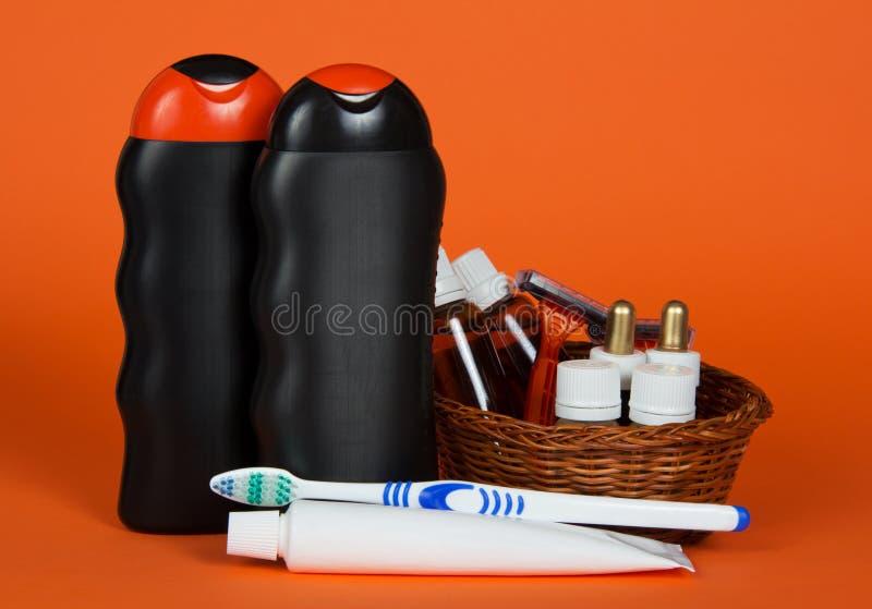 Shampoo, Gel, Kosmetik im Korb und Zahnbürste stockbild