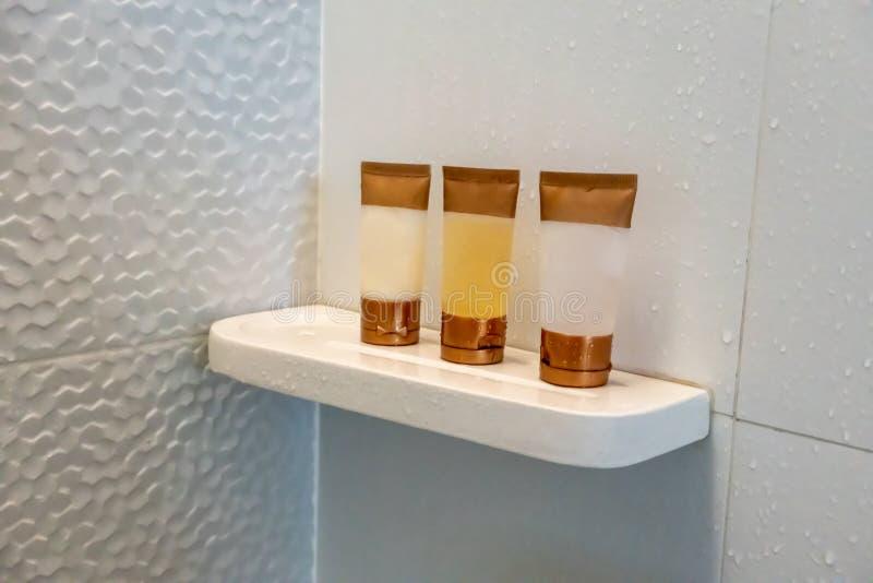 Shampoo, Pflegespülung und Duschgel auf Kunststoffrohr im Badezimmer lizenzfreies stockfoto