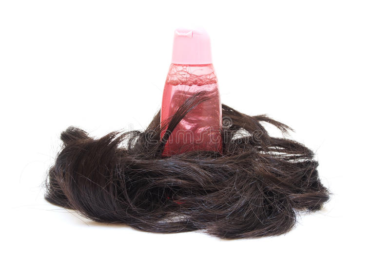 Shampoo in pink bottle and wig stock photography