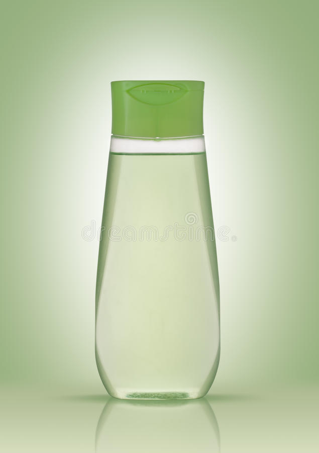Shampoo in a plastic bottle on a green background with reflection. The concept of purity and health.  stock image
