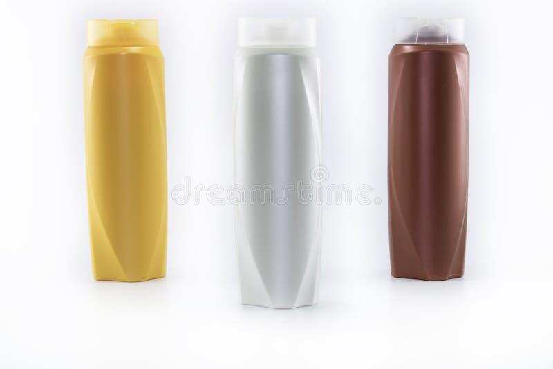 Shampooing, hydratant des bouteilles dans des couleurs brunes, blanches, jaunes photographie stock libre de droits