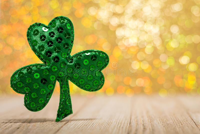 Shamrock on wooden board with beautiful gold bokeh room for text royalty free stock photos